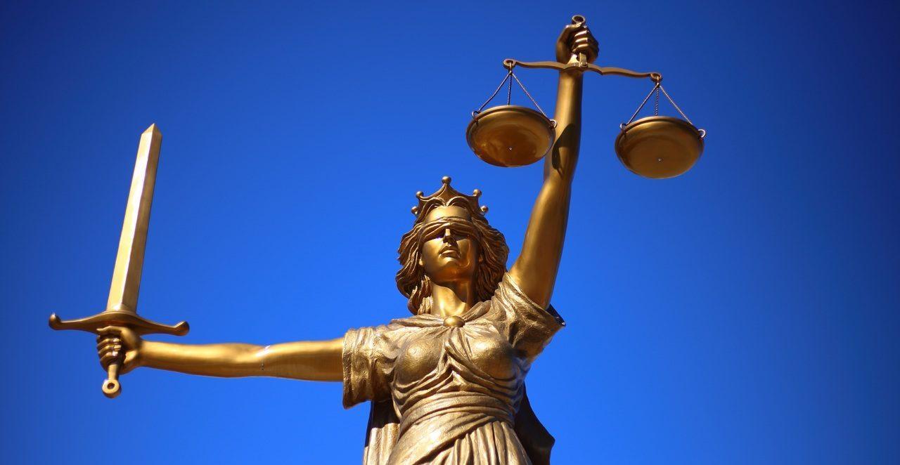 Oikeuden jumalattaren patsas, jolla on silmät sidottuna, miekka toisessa kädessä ja vaaka toisessa kädessä.